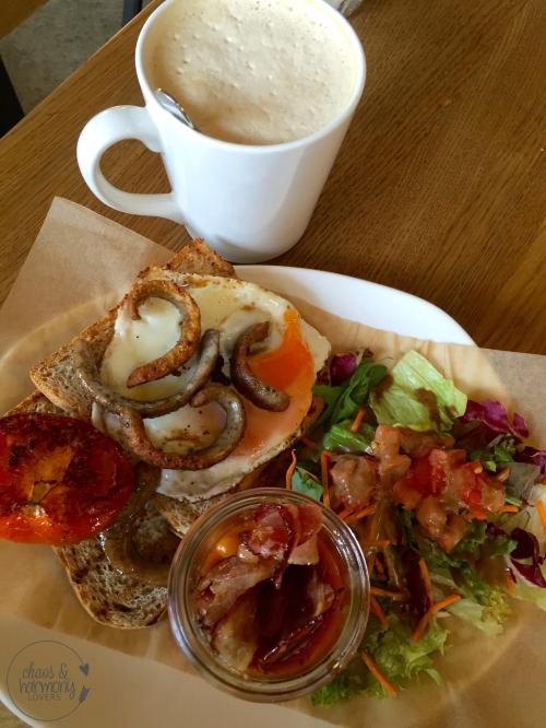 English Breakfast Spiegelei auf Toast, gebackene Bohnen im Glas, knuspriger Bacon, gebratene Nürnberger Würstchen und gegrillte Tomate